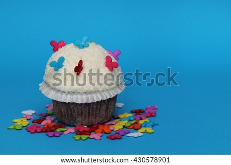 cupcake with colorful butterflies on blue background