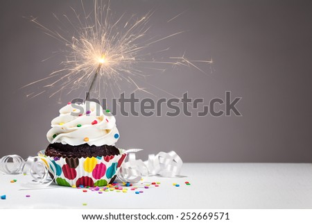 Cupcake with colorful sprinkles and a sparkler over a grey background.