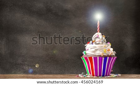 Cupcake with cream, candies and a candle on a wooden table with a blackboard background. Empty free copy space available. 3D Rendering - stock photo