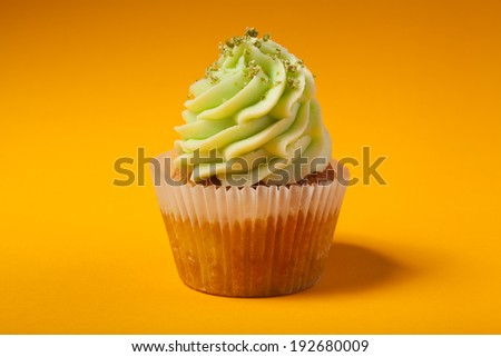 cupcake with cream isolated on orange background