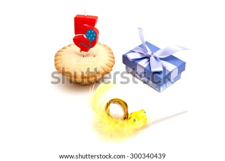cupcake with five years birthday candle, gift and whistle on white - stock photo