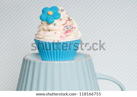 cupcake with flower and swirl on a blue cup - stock photo