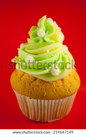Cupcake with green frosting on a red background.