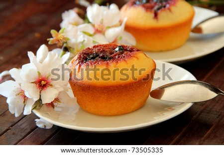 Cupcake with jam and a branch of almond tree on wooden background - stock photo