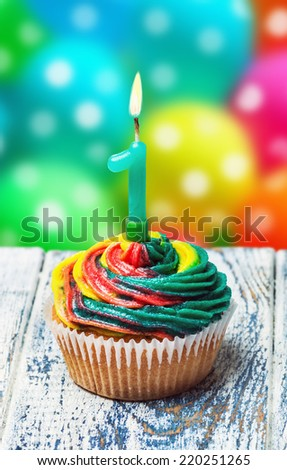 Cupcake with number one on the background of balloons. - stock photo