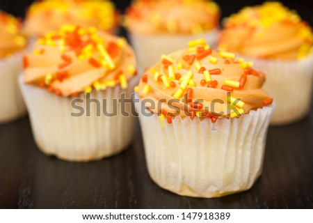 Cupcake with orange icing and yellow and orange sprinkles