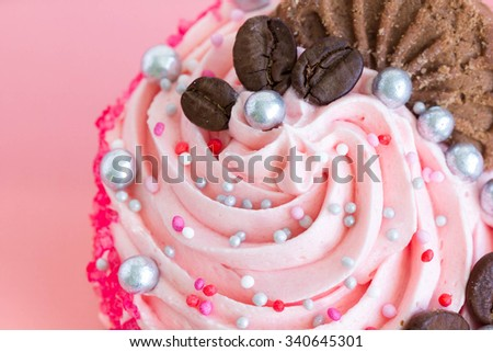 Cupcake with pink cream frosting and sprinkles, close-up - stock photo