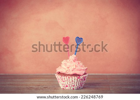 Cupcake with pink cream on a table. - stock photo