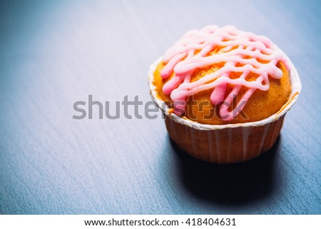 cupcake with pink frosting on  a wooden background - stock photo