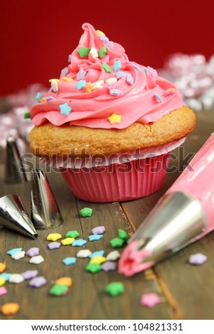 Cupcake with pink icing just being frosted and decorated - stock photo