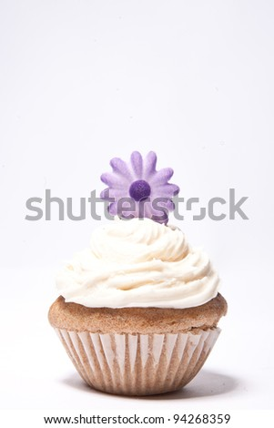 Cupcake with purple flower on top - stock photo