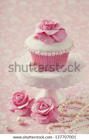 Cupcake with rose flower on a stand - stock photo