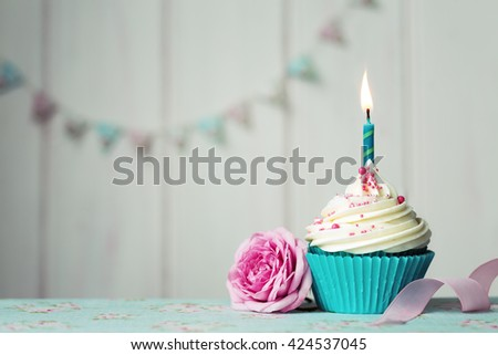 Cupcake with single candle and pink rose - stock photo