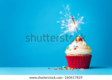 Cupcake with sparkler against a blue background - stock photo