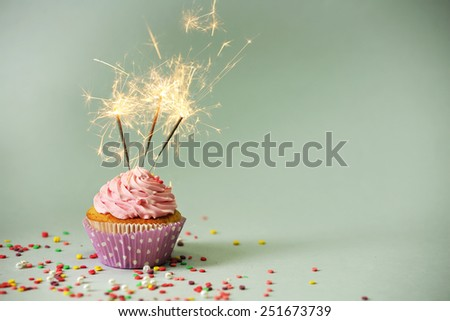 Cupcake with sparkler on grey background - stock photo