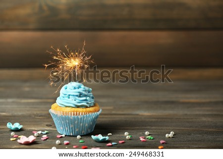 Cupcake with sparkler on table on wooden background - stock photo