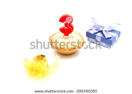 cupcake with three years birthday candle, gift and whistle on white - stock photo