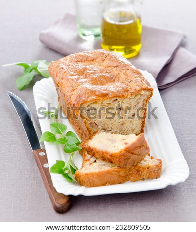 cupcake with tuna basil on a white plate with a knife next to a dark tablecloth - stock photo
