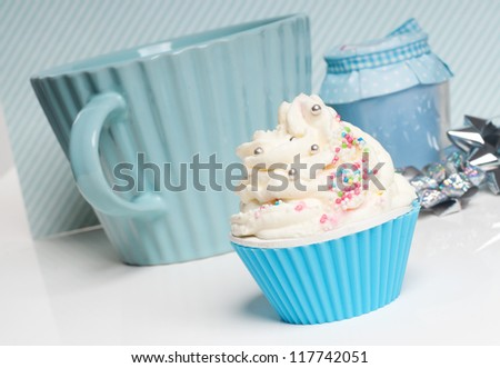 cupcake with whipped cream and an big cup in baby blue setting - stock photo