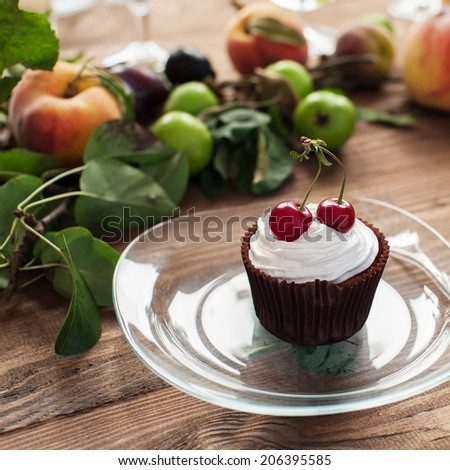 Cupcake with whipped cream and cherries on decorated wooden table, shallow DOF. - stock photo