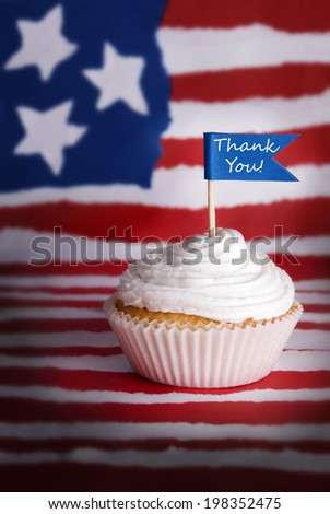 Cupcake with White Topping and Blue Flag with Thank You on it on an American Flag Background - stock photo
