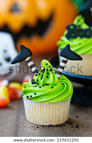 Cupcake with witch's legs - stock photo