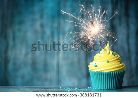 Cupcake with yellow buttercream and a sparkler - stock photo