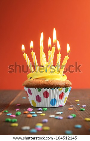 Cupcake with yellow icing full of yellow candles on orange background - stock photo