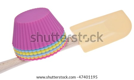 Cupcake wrappers and a spatula for an afternoon of baking. Isolated on white with a clipping path.