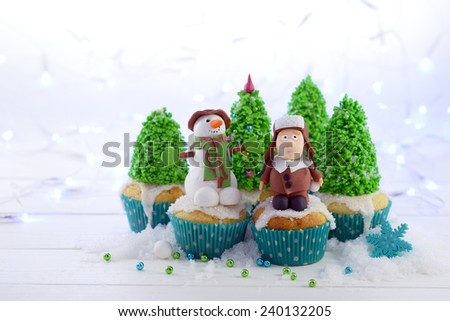 Cupcakes decorated with a sugar kid in a fur hat Snowman and trees on the Christmas lights background. - stock photo