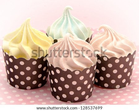 Cupcakes decorated with colored meringues - stock photo
