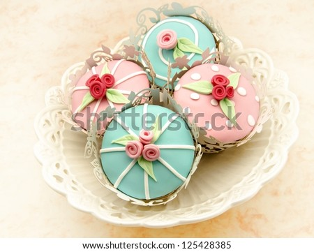 Cupcakes decorated with flowers - stock photo