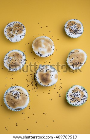 Cupcakes decorated with sprinkles and frosting - stock photo
