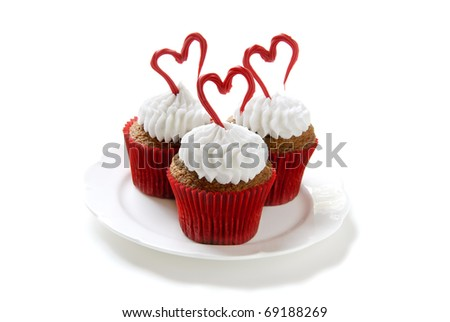 Cupcakes for Valentine's day. Chocolate cupcakes with vanilla frosting. Hearts made of red colored white chocolate. - stock photo