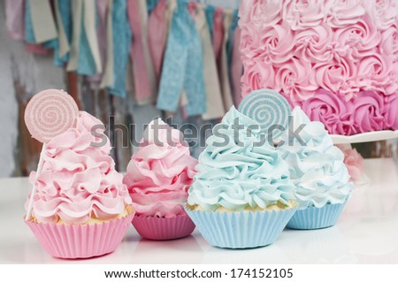 Cupcakes in pink and blue with garland and party cake - stock photo