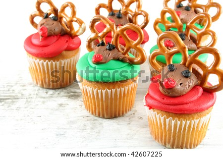Cupcakes of red and green decorated to look like Rudolph.  Shot with selective focus and a shallow depth of field. - stock photo