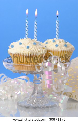 Cupcakes on glass stand with lit candles and streamers, gift in background