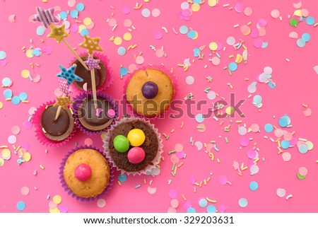 Cupcakes on pink confetti background - happy birthday card - stock photo