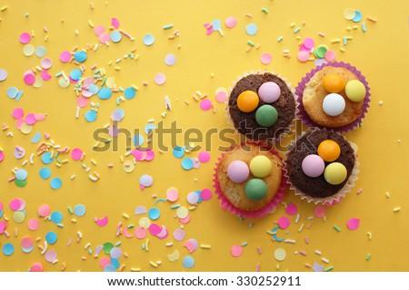 Cupcakes on yellow confetti background - happy birthday card - stock photo