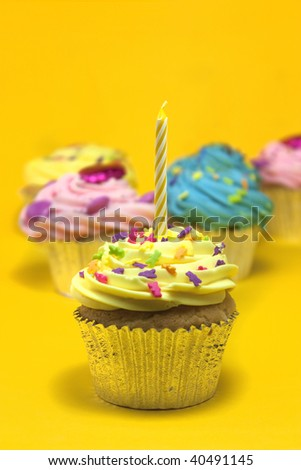 cupcakes shot on a yellow background with one candle - stock photo
