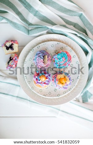 Cupcakes with blueberry jam decorated with cream cheese on a wooden background