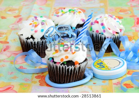Cupcakes with one decorated with a baby boy theme.  Blue booties and candle on top with ribbons and a Boy rattle. - stock photo
