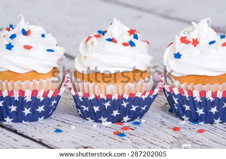 Cupcakes with patriotic 4th of July sprinkles on vintage background - stock photo