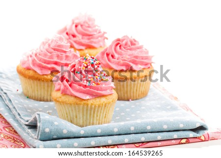 Cupcakes with pink frosting and colorful sprinkles - stock photo