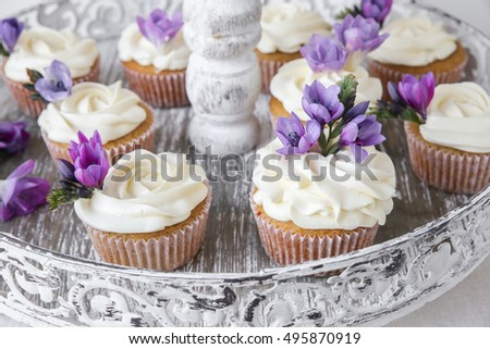 cupcakes with purple edible flowers on vintage cake stand for tea party