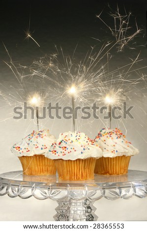 Cupcakes with sparklers on glass cake stand - stock photo