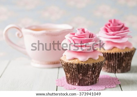 Cupcakes with sweet rose flowers and a cup of tee