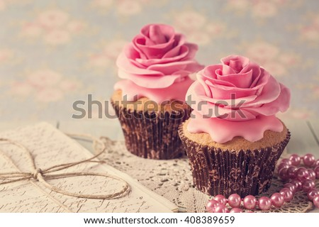 Cupcakes with sweet rose flowers and a letter - stock photo