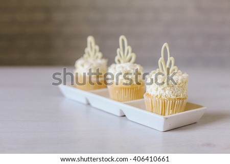 Cupcakes with white chocolate and coconut, on the vintage table.