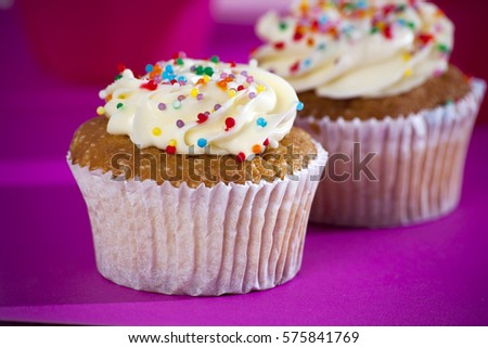 Cupcakes with white cream on the pink background, arranged for a party or a wedding reception